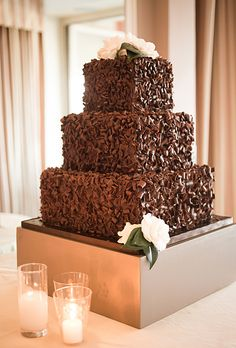 Brides.com: . A Three-Tier Wedding Cake Covered in Chocolate Shavings. Los Angeles-based The Butter End Cakery whipped up Kaley Cuoco's show-stopping, upside-down wedding cake—it hung from a chandelier!—as well as this chocolate shaving-covered, three-tiered wedding cake. It looks like a giant chocolate truffle, and that's just the way we like it.  See more square wedding cakes.
