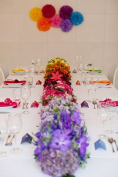 rainbow  centerpiece with matching plate/napkin/utensils settings in front of flowers on a white  tablecloth looks great