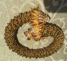 Unusual vintage costume snake bracelet has jeweled classical dolphin heads on either end and twisting rows of gold tone beads in between. The dragon like heads are decorated with white and red rhinestones. Fits most wrists.