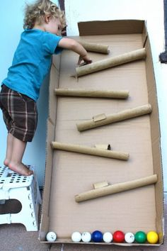 Fun! A ball maze created from a cardboard box and paper towel rolls.