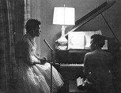 """Billie Holiday and Hazel Scott enjoy each other's company at party in 1957. In """"Lady Didn't Always Sing the Blues,"""" a 1973 article in Ebony magazine, her friend Ms. Scott said, """"The thing I hope the kids don't miss – the ones who are just discovered Lady – is that she took a lot of the tragedy of her life and made something beautiful out of it; something very beautiful."""" The photo was taken by the legendary photographer Roy DeCarava (1919-2009)."""