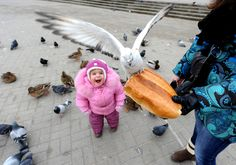 Mother and her child feed birds in the Belarus capital Minsk, on February 6, 2014.