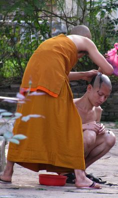Shaving head of novice monk . Laos