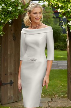 Short fitted dress that features a wide boat style neckline. The dress has an added diamante detail on the waist to give that added sparkle. The dress is finished off with elegant elbow length sleeves. Colours: Stone