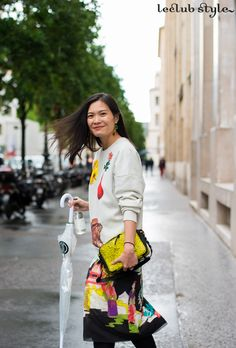 Street Style portraits by Ángel Robles. Fashion Photography from Paris Fashion Week. Smiling woman wearing a printed skirt and sweatshirt after Paul Smith fashion show, Paris.