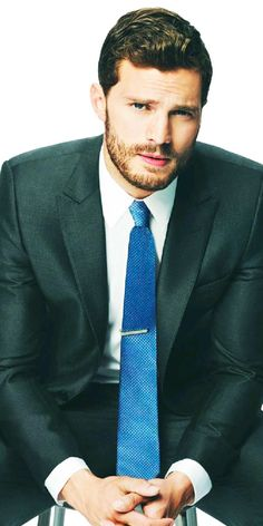 Inscrutable stare paired with a blue tie to match his eyes.   Christian Grey
