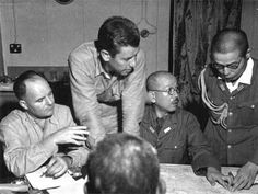 Rogers, Wolf, Ishii n a conference held on board the Mt. McKinley prior to the landing, BGen William W Rogers, V Amphibious Corps Chief of Staff, left, stresses a point to his interpreter, Maj F. D. Wolf, as RAdm Keichi Ishii, Chief of Staff of Sasebo Naval Station and his vice chief locate a point under discussion. National Archives Photo 127-N-139194