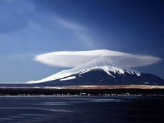 Lenticular cloud, Mt. Fuji, Japan.  Altocumulus lenticularis is one of the more obviously bizarre cloud types. They often form above or near mountains, as moist air flows rapidly over a rise in elevation.