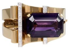 "A Retro gold, amethyst, and diamond bangle bracelet, the open tapered front featuring curved and scroll motifs set with a large rectangular amethyst and square-cut diamond accents, in 14k. Designed by MGM's Gilbert Adrian for Joan Crawford. Inscribed, ""Dearest, the third step on our bridge you have built so well. I love you forever and a day - Phillip. 21 July 1945."""