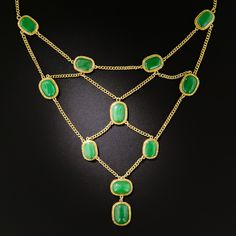 Natural Burmese Jadeite Festoon Necklace. A collection of fourteen matched, natural, deep apple green jade cabochons, each framed in a hand engraved 18K gold bezel, are artfully arrayed in this rare and wonderful swag necklace hailing from 1930s-40s China or Hong Kong; however, the jades are very likely much, much older. The clasp is emblazoned with the Chinese characters for Blessings/Good Luck
