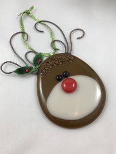 **New for 2017** Fused glass red-nosed reindeer ornament, hand cut by me and kiln fused twice. Shades of brown and almond glass make up the head. Hand made glass marbles are added for his eyes and nose, and shades of brown frit for texture on top of his head. Copper wire is used to create his antlers. Burned in the kiln and wire-brushed after, the copper takes on a rustic appearance. Mini lacquered imitation holly leaves and berries are added to finish his holiday look. Aanraku bail and…