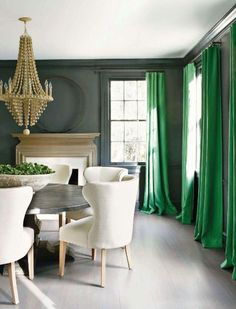 Dining room with kelly green curtains against gray walls.