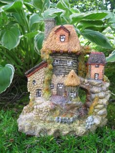 """HAZELNUT FAIRY HOUSE   This 3 story fairy house with many windows, doors, thatch roof, guest cottage and root cellar.   A small fenced area and bridge are in the front and a cobblestone path surrounds the house.         Approx. size  6"""" x 7"""" $24.99"""