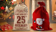 """Large Festive Christmas Gift Sacks - 2 Designs Channel everyone's favourite gift-giver with the Large Christmas Gift Sacks      Fill with presents and treats for your loved ones      Choice of two vintage-style designs      Hessian-coloured bag with drawstring and """"Do Not Open Until 25th December"""" slogan      Size: 79cm (H) x 50cm (W) approximately      Or a red nylon bag with cute Santa..."""
