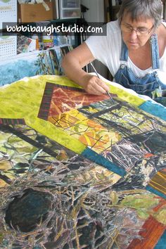 In my studio in DeLand Florida. Work in Progress – Collaging an art quilt that combines hand printed fabrics, gel medium photo transfer. Acrylics on textiles.
