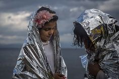 Two girls wear thermal blankets provided by volunteers after their arrival on the Greek island of Lesbos