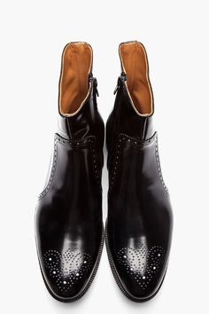 MAISON MARTIN MARGIELA //  Black Patent Leather Semi-Brogue Boots  32168M047001  Calf-high patent leather boots in black. Round toe. Perforated decoration at toe and midrow. Zip closure at inner side. Black foxing. Tonal stitching. Leather upper, leather sole. Made in Italy.  $1200 CAD