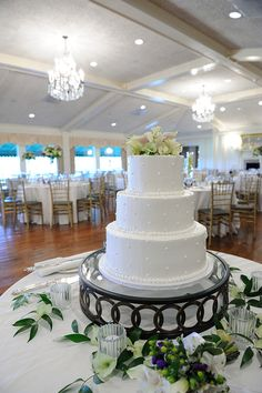 A simple wedding cake rests atop a dark cake tray at one couple's wedding reception in the Oakmont Country Club, Pittsburgh. The three-tiered cake was detailed with soft, white polka dots and a dotted trim at the bottom of each layer. Calla lilies grace the top. In the distance, the ballroom is arranged with round tables dressed in white and surrounded with gold chairs. The Dreamscape Band entertained the couple and their guests at the party. http://www.dreamscapeband.com/weddings.html