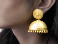 These earrings never go out of trend! A gold plated jhumka set by Roopa Vohra on strandofsilk.com featuring an alluring all over embossed design and the domes studded with tiny gold danglers at the ends. Wear it with a kanjeevaram or a cotton silk saree to look glamorous! #glamorous #indianjewellery #gold #earrings #roopavohra #strandofsilk #jewelry