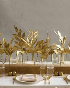 What a neat centerpiece! Gold spray painted leaves tucked into holes drilled into a stained and sealed length of four-by-four. Not difficult to make. I would go with a dark stain, maybe even a reddish tone, and a combination of silver and gold leaves. Or wire a selection of both gold and silver to a single stem of florist wire.
