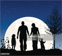 Joven familia en la noche en silueta en contra de la luna