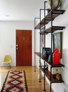 Whether you're going for a sophisticated, modern vibe or a homey, rustic appeal, industrial pipe shelves can be one way to accomplish both of these desired looks. Many people decide to build their own industrial pipe shelves that incorporate these aesthet Pipe Bookshelf, Diy Pipe Shelves, Pipe Shelving, Bookshelf Ideas, Shelving Display, Book Shelves, Bookcase Plans, Wall Shelves, Bookshelf Design