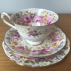 "Royal Albert Vintage Teacup Trio Pattern ""Serena"" A gorgeous teacup, saucer and plate in the avon demi-tasse shape by Royal Albert. This set has beautiful floral garlands with large pink roses, purple, orange, yellow and blue flowers and lots of green foliage. This set is trimmed in gold."