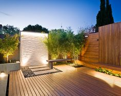 Like the use of uplights, decking mixed with gravel and concrete stepping stones.