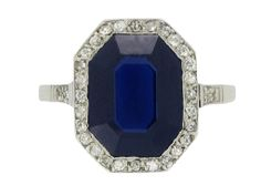 Sapphire and diamond cluster ring. Set with a natural unenhanced octagonal step cut sapphire in an open back millegrain setting with an approximate weight of 3.50 carats, encircled by a single row of round old single cut diamonds and further set to the shoulders, thirty two in total in open back grain and millegrain settings, to an elegant octagonal cluster with an ornate openwork gallery, intricate cheniers and ridged shoulders, flowing down to a solid flat shank. Tested platinum, circa…