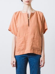 Marvel Top: Boxy and oversized top in salmon colored linen with two large patch pockets at front and a slit neckline. Short sleeves Oversized silhouette Center seam down front and back Straight hem 100% linen