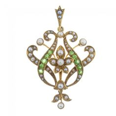 An early 20th century 15ct gold seed and split pearl and demantoid garnet pendant. Of openwork design, the seed and split pearl flower, within a split pearl and circular-shape demantoid garnet scrolling surround, suspending a split pearl drop. Length 4.1cms. Weight 5gms. : Lot 45