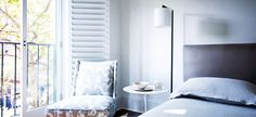 Hues of gray and purple in the bedroom with balcony that's open and shuttered doors