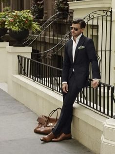 i thought that black suits will never fits with brown shoes... but i may wrong. but what's the tips for this picture?why it looks fit well with brown shoes?is it because of the brown bags?