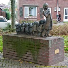 "The Pied Piper of Hamelin  -  Bonze statue of a flute playing ratternvanger behind him with 17 children on a brick plinth.  Presented to the council of Hellevoetsluis by the Building Society ""Housing"" On March 1, 1962."