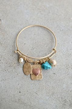 Charming Love Bracelet from Page 6 Boutique | We are O B S E S S E D with charm bracelets and this one by Golden Stella is no exception! We are smitten with the details adorned on this matte gold beauty. Features an iridescent pearl, hammered oval charm, copper heart on a similar hammered rectangle, turquoise stone, and finally--a shiny gold ball. Seriously...could it get anymore perfect?! Stack with any one of our fabulous bracelets. Lead compliant.