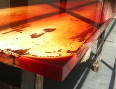 The shiny, smooth surface of the tables is achieved by pouring coloured epoxy onto the uneven surface of a wooden table. Depending on the waves, grain and varying depths of the wood, the colour of the resin can be more or less intense.