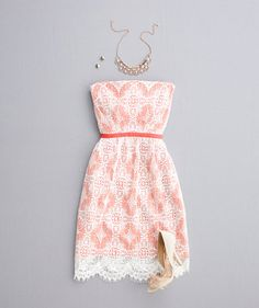 Orange and white strapless lace dress with neutral heels and jewelry via real simple