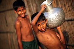 town of Sittwe in Rakhine State, near the Myanmar boarder with Bangladesh. The state has a minority population of Muslim Rohingya people whose freedom of movement is severely restricted and the vast majority of them have been denied Myanmar citizenship since they are not genuine tribe of Burma. Rohingya boys carrying water in one of the muslim neighbourhoods of Sitwee.