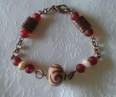 Bracciale con perle di vetro rosse e sabbia, minuteria color bronzo... (5,00)