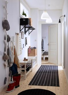 A small hallway with two benches for shoes, a mirror and tree-shaped hangers for jackets and bags, all in white.