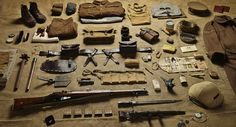 Equipment of a British Sergeant in the Battle of the Somme, 1916. On the left is a Trench Club for close-quarters combat. The mess kit contains a knife, fork, spoon, shaving brush and a button stick to prevent Brasso from getting on a uniform polishing brass buttons. The covered steel helmet is the 1915 Brodie design, a million of which were produced in a year.