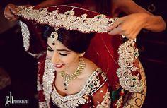 Desi bride wearing veil on wedding day. Beautiful bordering on red veil.