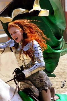 Modern woman in armour, riding a horse in battle style and waving a banner.