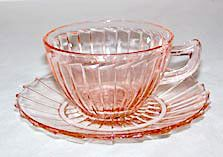 These are Depression Glass cup and saucer sets in the Sierra or Pinwheel pattern made by Jeannette. They are in good condition with no chips or cracks.