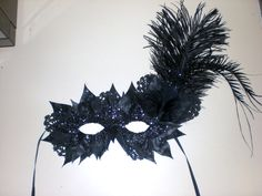 homemade masquerade mask! painted fake leaves, black glitter, painted doilies, and feathers!!!