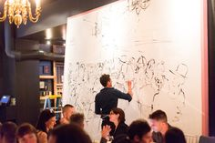 As guests dined, artist Blue Logan painted the scene on a large canvas set up along one wall of the dining room.