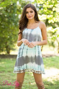 This tie dyed dress is perfect for your next music festival or summer fair! The pattern features an unconventional combination of grey, turquoise, and white for a more understated color scheme. However, this dress is anything but dull - the bold pattern really stands out in a crowd! The tassels on bottom hemline add a cute boho twist to the dress, while the textured material and scoopneck keep it comfortable and easy to rock.