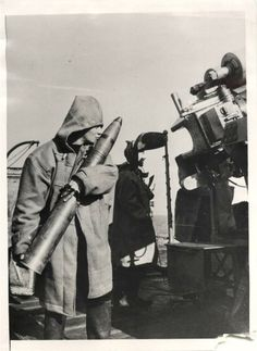 1940 - Anti-aircraft gunner aboard a British destroyer bestows a kiss on shell before loading into gun.