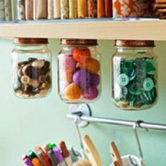 Jar lids stuck under shelves for cottons, buttons etc at sewing station - just unscrew jar....genius!