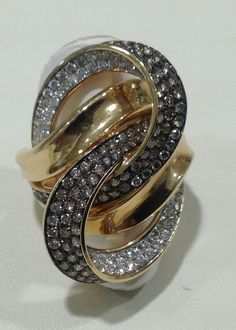 Here we have a very intricately designed natural chocolate and white diamond ring set in 14k yellow gold. This gorgeous ring is very unique and is definitely a conversation piece. If interested, please call. Ref#10098230.